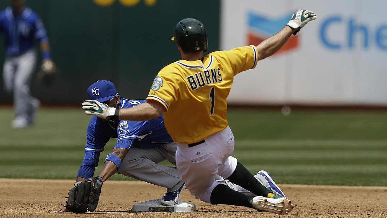 Kansas City Royals Alcides Escobar, left, tags out Oakland Athletics Billy Burns (1) in the third inning of a baseball game June 28, 2015, in Oakland, Calif.  (AP Photo/Ben Margot)