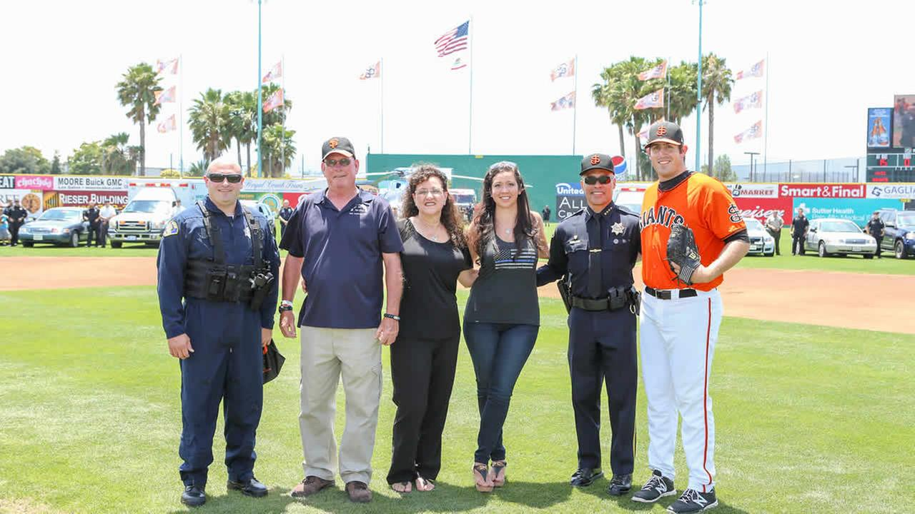 SJ Giants RHP Dan Slania, SJPD Chief Larry Esquivel, and tactical flight observer Chuck Moggia stands with the family of Ofc. Michael Johnson in San Jose, Calif. on June 28, 2015.Tim Cattera/San Jose Giants