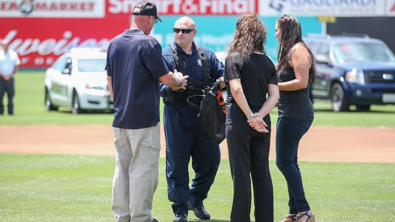The family of fallen Officer Michael Johnson receives the ceremonial first pitch ball at a San Jose Giants game in San Jose, Calif. on June 28, 2015.Tim Cattera/San Jose Giants