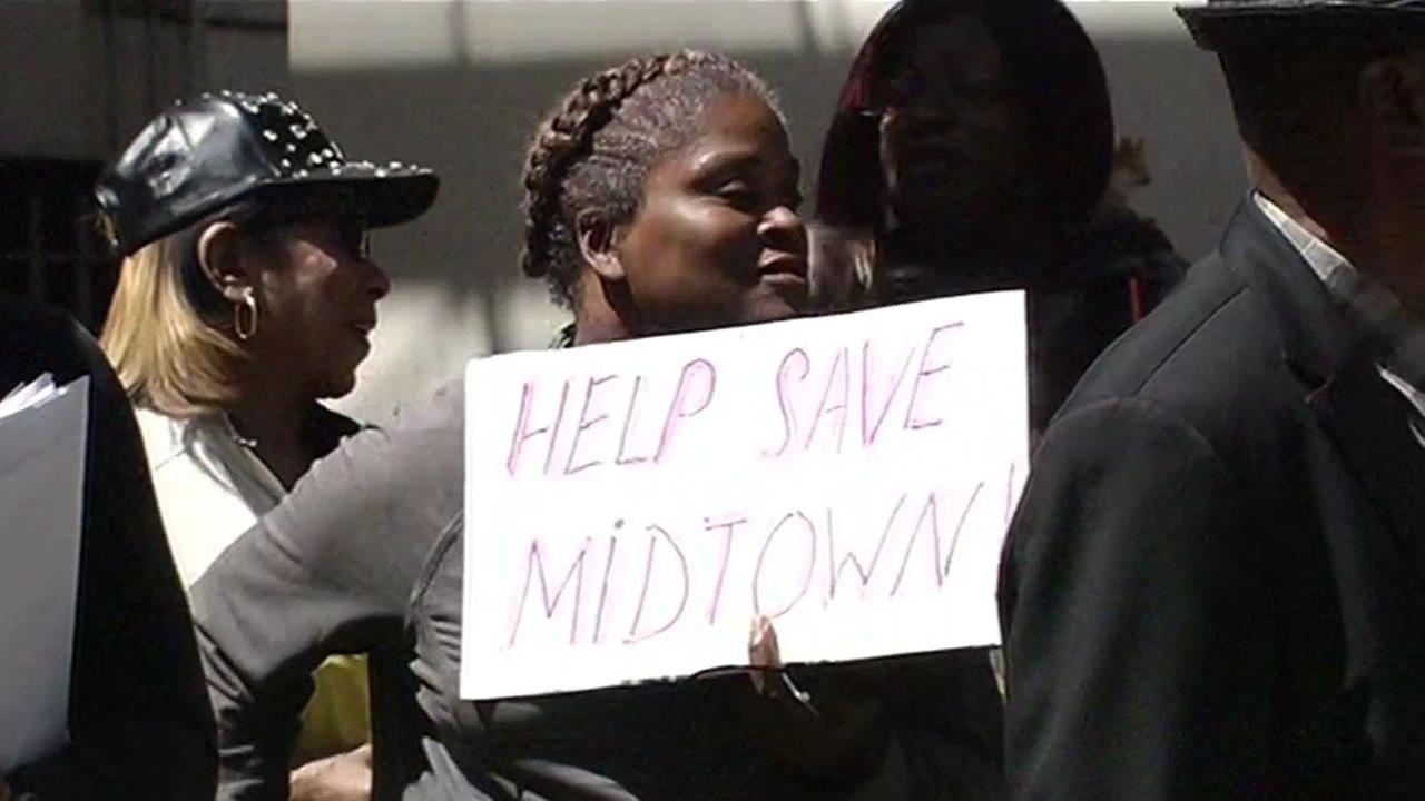 A San Francisco resident holds a sign that says, Help Save Midtown, to protest rising rents at the Midtown Park Apartment complex.