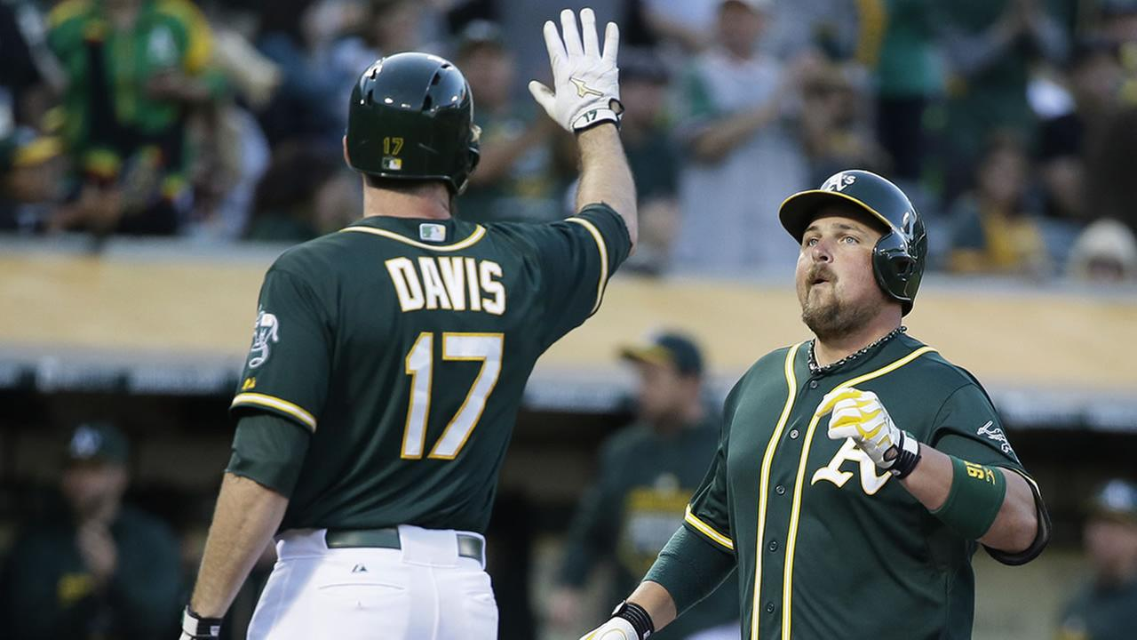 Oakland Athletics Billy Butler high fives teammate Ike Davis