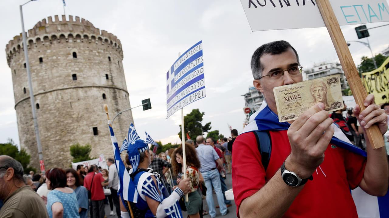 Protest holds an old 1,000 drachma bank note during a rally in the northern Greek port city of Thessaloniki, Monday, June 29, 2015.