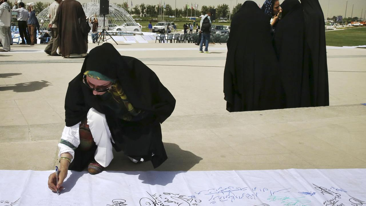 An Iranian woman signs a petition during a demonstration demanding Iran signs a good deal that reserves rights of the Iranian nation, in Tehran, Iran, Tuesday, June 30, 2015.
