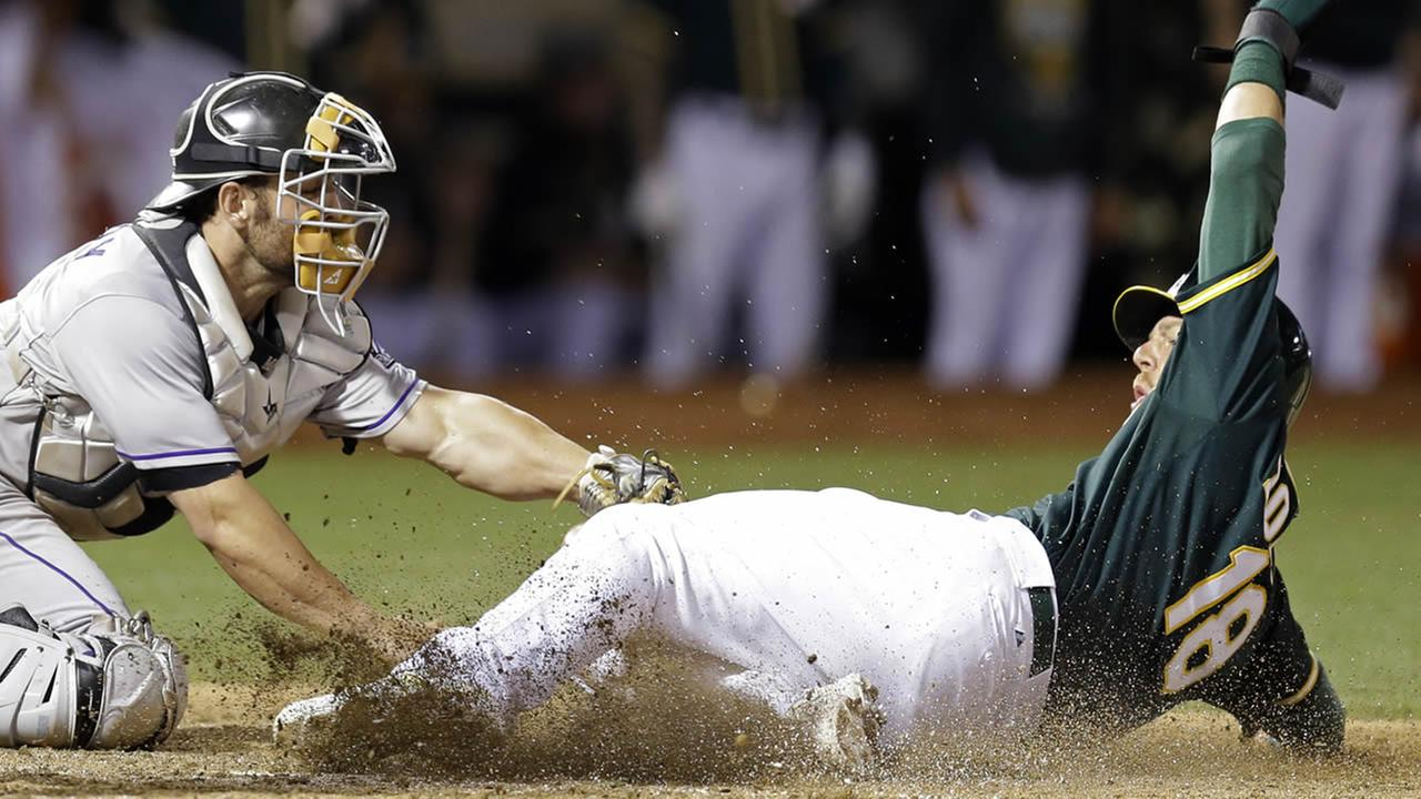 Oakland Athletics Ben Zobrist slides to score