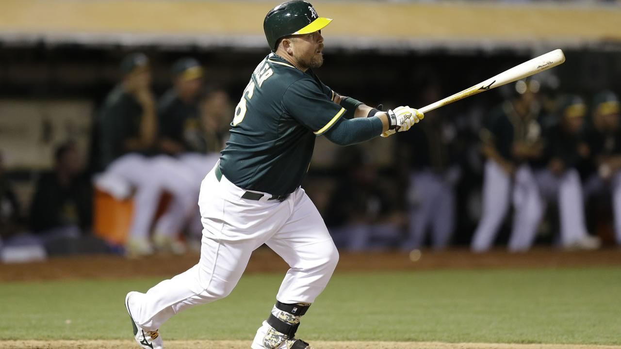 Oakland Athletics Billy Butler swings for an RBI single off Colorado Rockies Tommy Kahnle during the eighth inning of a baseball game Tuesday, June 30, 2015, in Oakland, Calif.