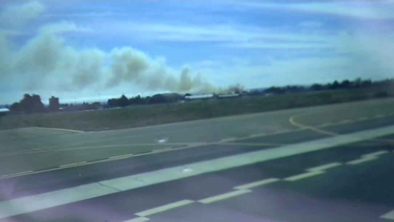 An image from cellphone video shows a large plume of smoke from a brush fire in Hayward, Calif. on July 5, 2015.