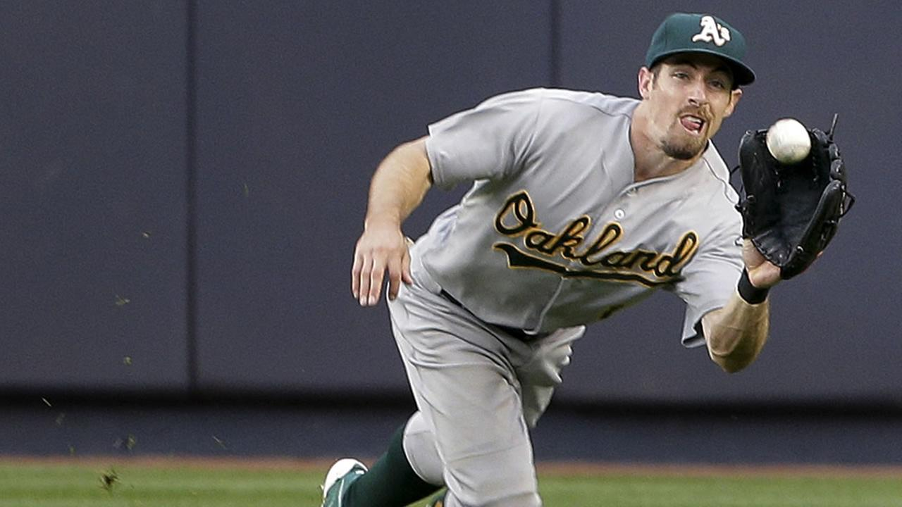 Oakland Athletics center fielder Billy Burns makes a lunging catch on a ball hit by New York Yankees John Ryan Murphy during the third inning of a baseball game.