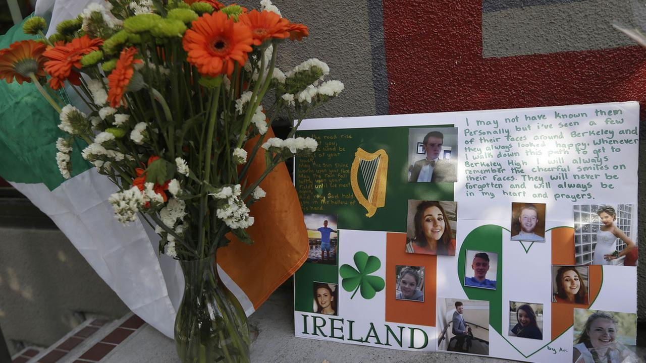 A flag of Ireland, flowers and a sign are shown at a shrine left for victims of the Library Gardens apartment building balcony collapse Wednesday, June 17, 2015.