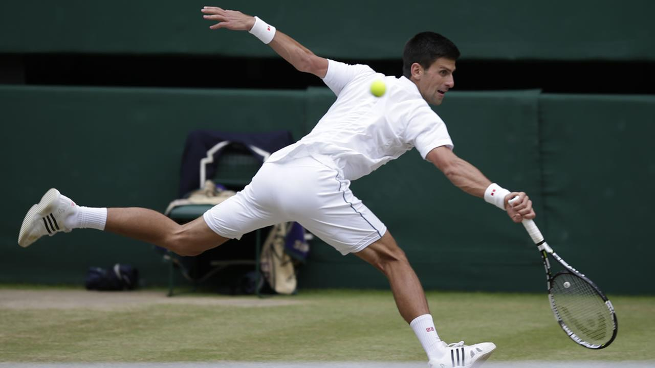 Novak Djokovic returns a ball to Roger Federer during the mens singles final at the All England Lawn Tennis Championships in Wimbledon, London, Sunday July 12, 2015.