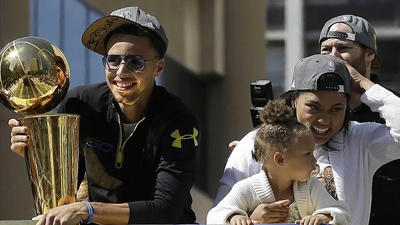 Warriors guard Stephen Curry rides a bus with his daughter Riley, and wife Ayesha during a parade winning the NBA championship in Oakland, Calif. on Friday, June 19, 2015.