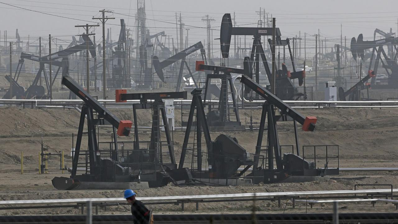 In this January 2015 file photo, a person walks past pump jacks operating at the Kern River Oil Field in Bakersfield, Calif.