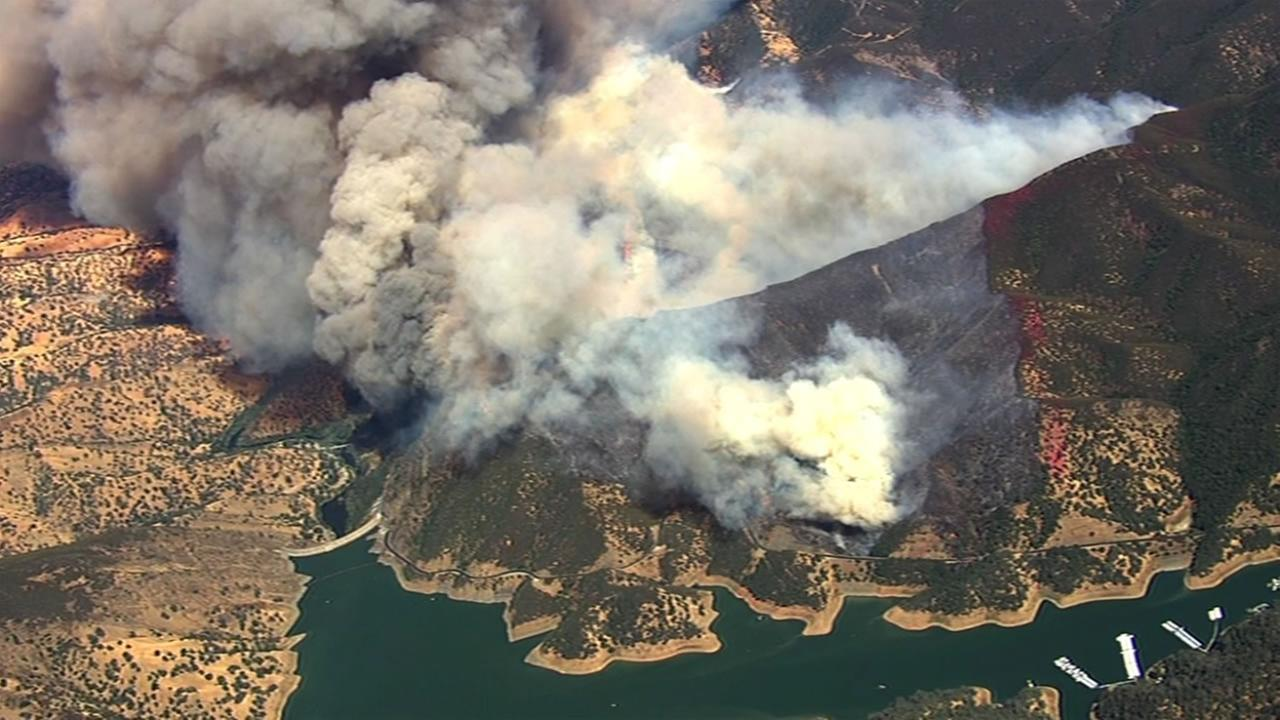 A large fire burning south of Lake Berryessa is threatening structures and closing roads in the area, July 22, 2015.