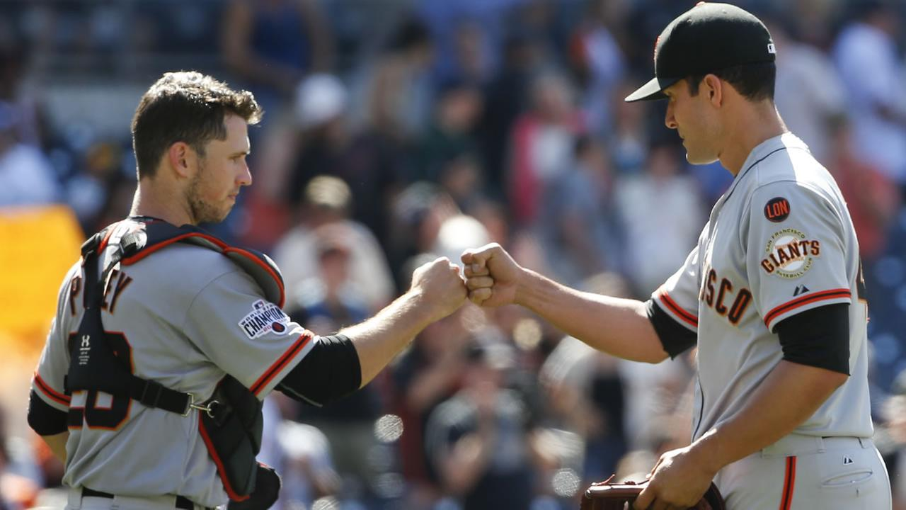 San Francisco Giants catcher Buster Posey, left, knocks knuckles with Javier Lopez after their 7-1 victory over the San Diego Padres in a baseball game Wednesday, July 22, 2015.
