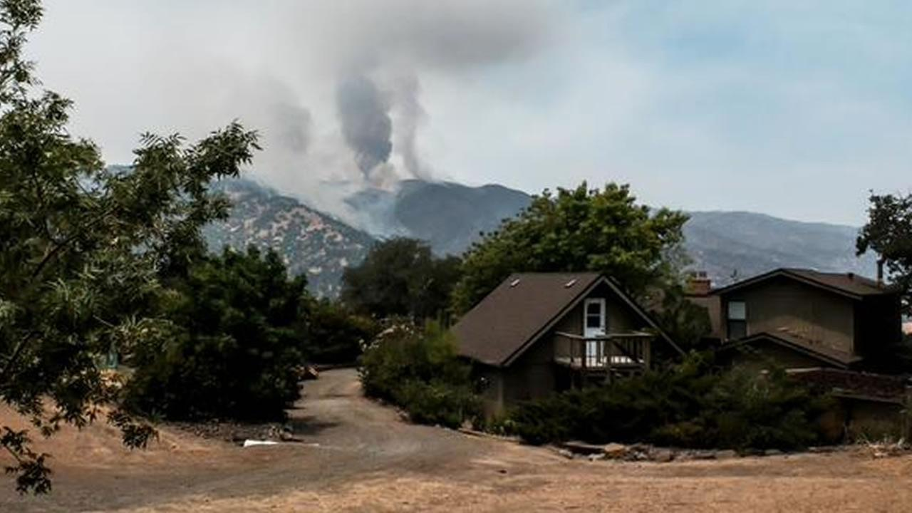 Residents watch as a large fire burning south of Lake Berryessa is threates structures, forces evacuations and closes roads in the area, July 23, 2015. KGO-TV