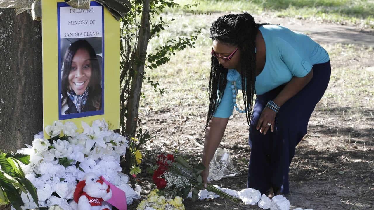 Jeanette Williams places a bouquet of roses at a memorial for Sandra Bland near Prairie View A&M University, Tuesday, July 21, 2015, in Prairie View, Texas.