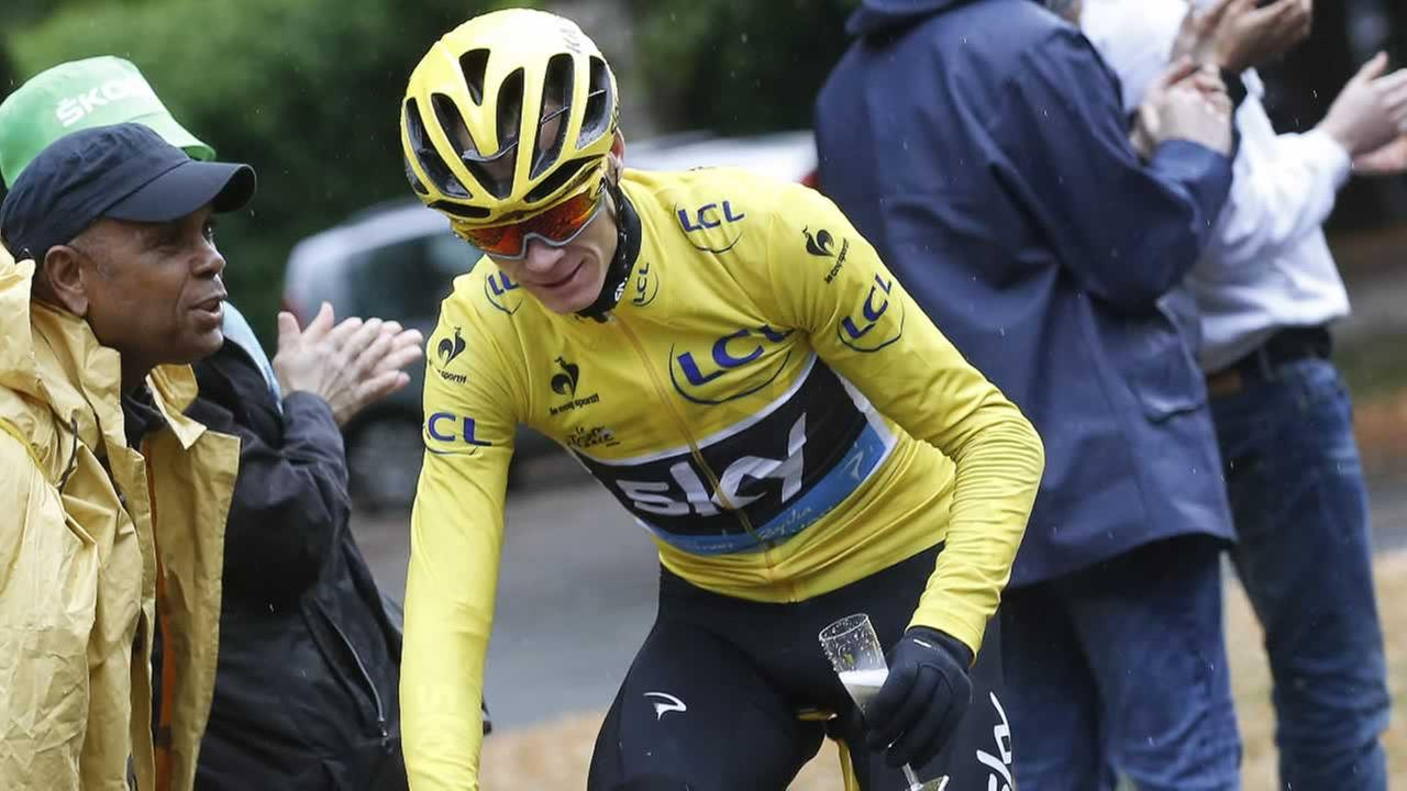 Britains Chris Froome rides with a glass of champagne after the last stage of the Tour de France cycling race over 109.5 kilometers in Paris, France, Sunday, July 26, 2015.