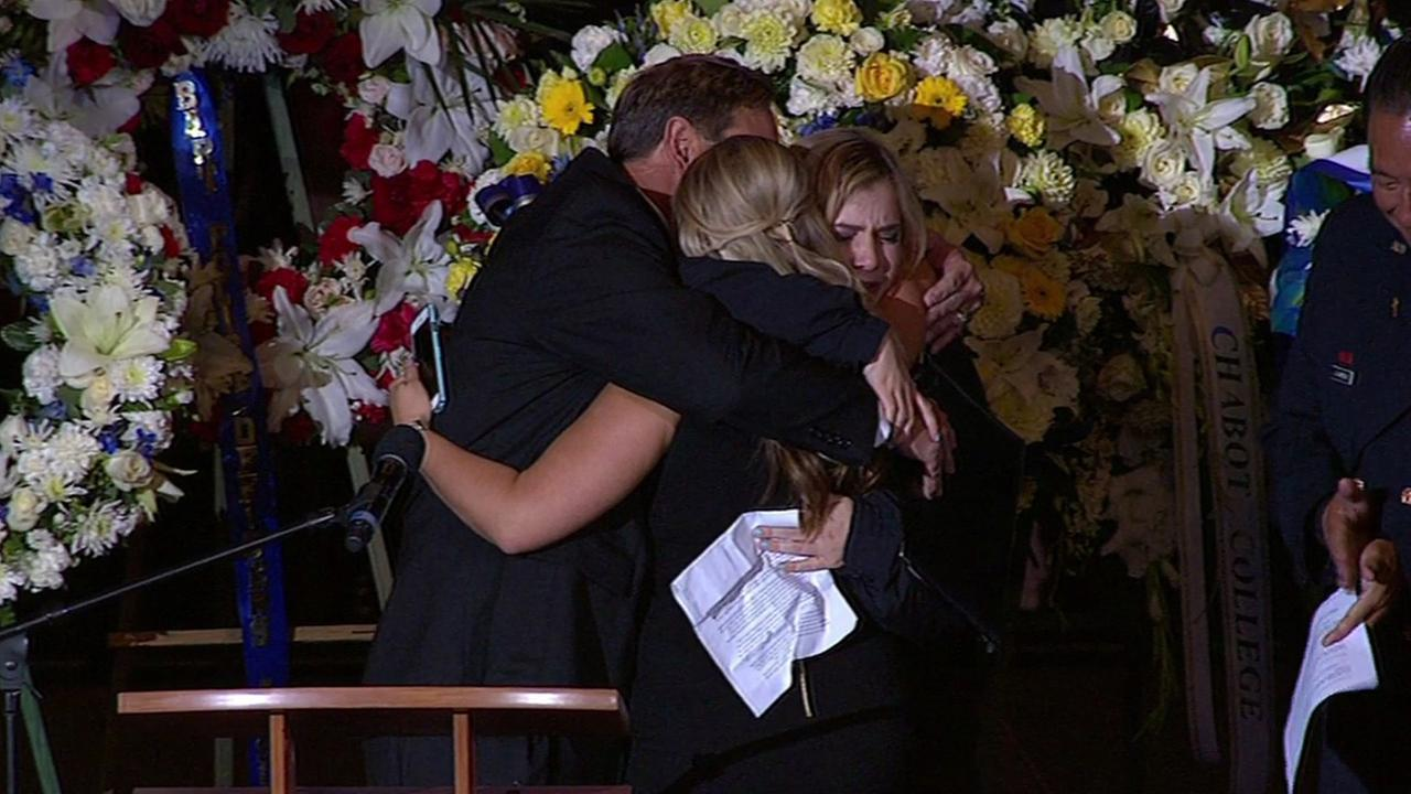 Sergeant Scott Lungers two daughters and his older brother embrace on stage at his memorial at Oracle Arena in Oakland Calif. on Thursday, July 30, 2015.