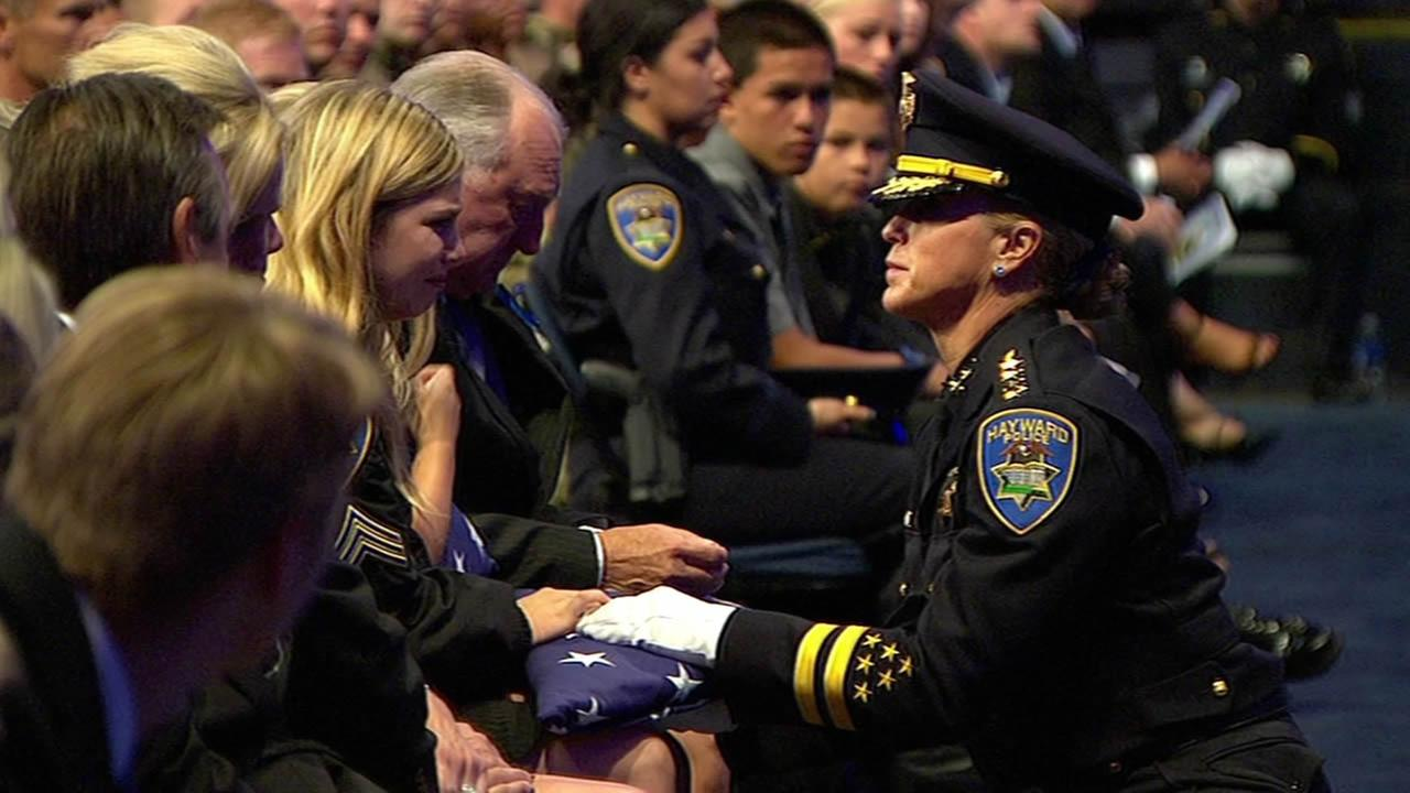 Hayward Police Chief Diane Urban presents an American flag to fallen Sgt. Scott Lungers father and daughters at Oracle Arena in Oakland, Calif. on Thursday, July 30, 2015.