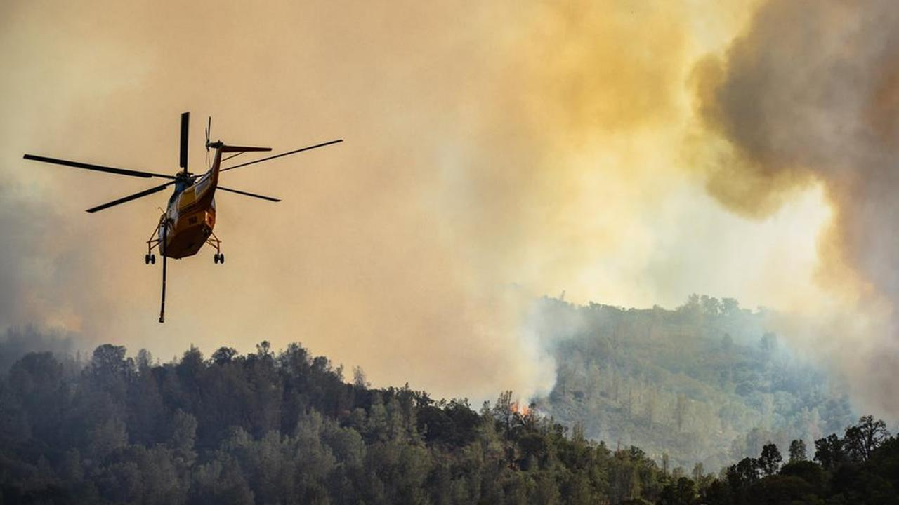 A helicopter flies through smoke from the Rocky Fire thats burning in Lake County, Calif. on Monday, August 3, 2015.