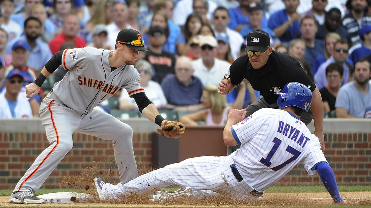 Cubs Kris Bryant (17) is safe at third base on a wild pitch as Giants third baseman Matt Duffy (5) makes a late tag during a game, Aug. 7, 2015, in Chicago. (AP Photo)