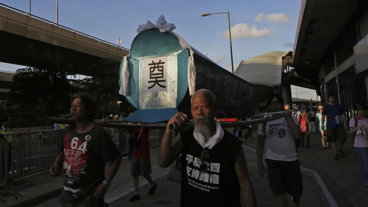 Protesters carry a mock coffin march in Hong Kong, Sunday, June 1, 2014, to mark the 25th anniversary of the bloody crackdown on Tiananmen Square. (AP Photo/Vincent Yu)