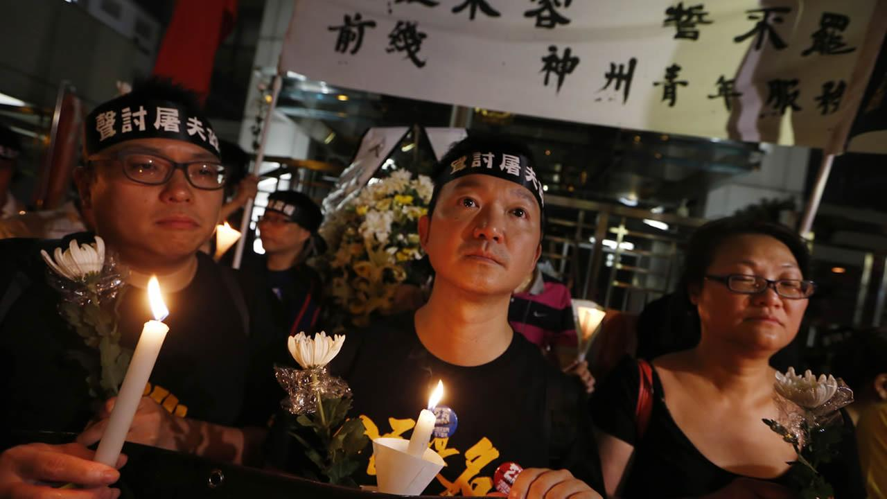 Protesters wear headbands with a slogan reading Denounce butcher regime as they attend a candlelight vigil in Hong Kong, June 3, 2014. (AP Photo/Kin Cheung)