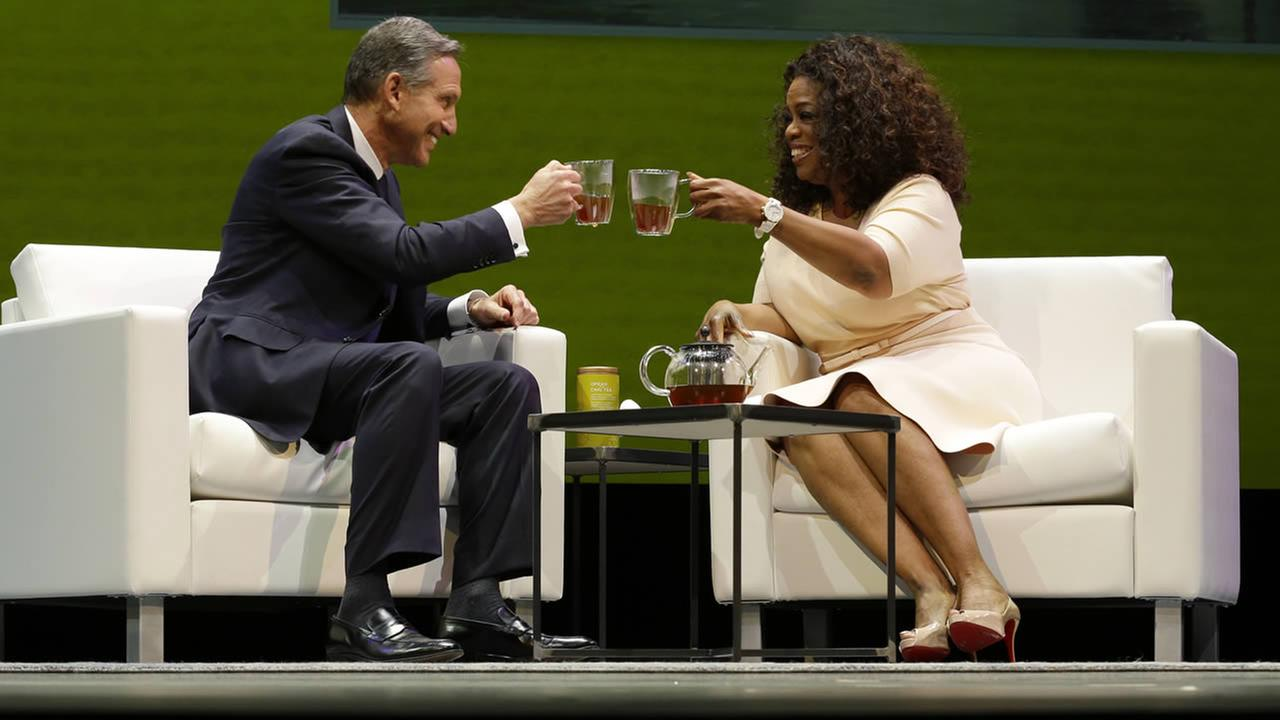 Howard Schultz, left, chairman and CEO of Starbucks Coffee Company, clinks tea cups with Oprah Winfrey, right, to announce their partnership to offer Teavana Oprah Chai tea