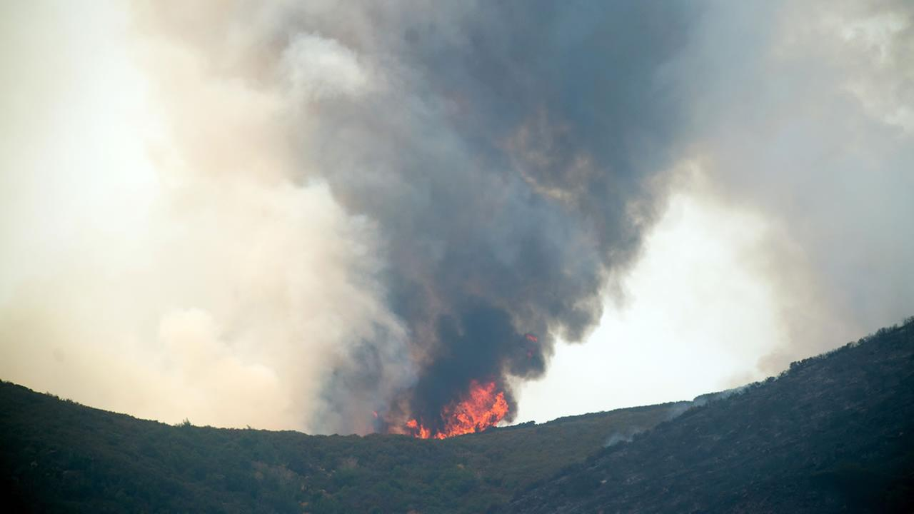 Smoke and flames rise from a ridge top as the Wragg fire burns near Winters, Calif., on Thursday, July 23, 2015.