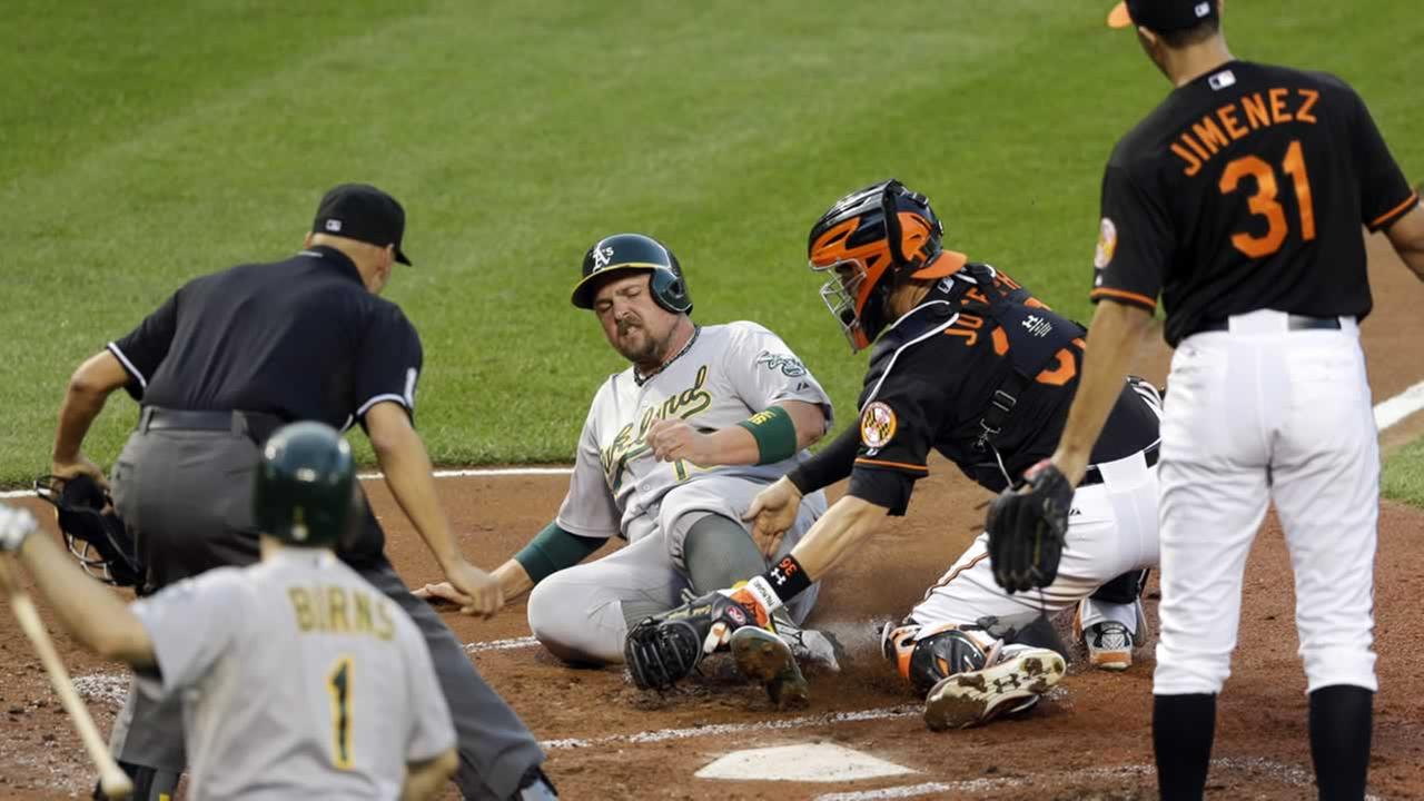 Orioles catcher Caleb Joseph tags out Athletics Billy Butler on a single by Marcus Semien during the second inning of a baseball game, Friday, Aug. 14, 2015, in Baltimore.