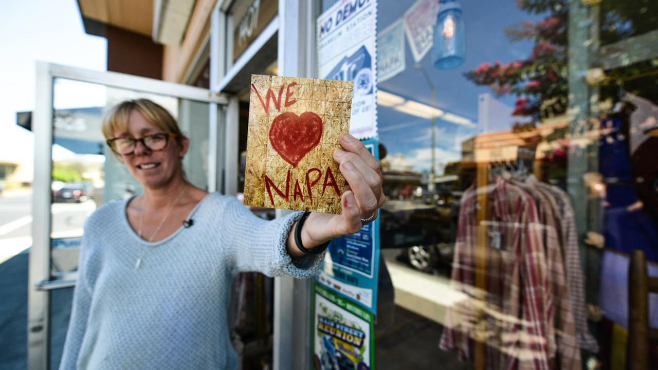 On August 11, 2015, Patricia Trimble holds a postcard that helped pay for a quake-damaged window in her Napa, Calif. store. She took a photo, made the card, and sold them for $1.KGO-TV/Wayne Freedman