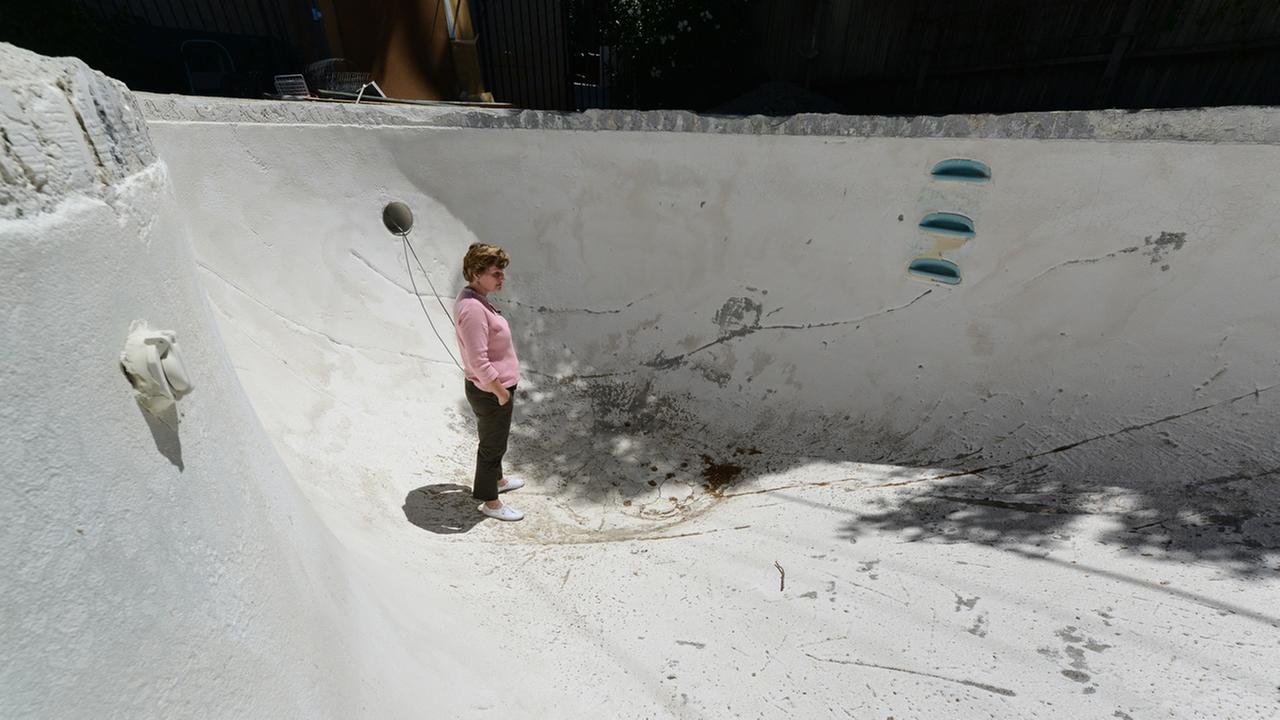 Elizabeth Emmett stands in her pool filled with cracks in Napa, Calif. on August 11, 2015.  A new fault line runs directly beneath that pool and her home. KGO-TV/Wayne Freedman