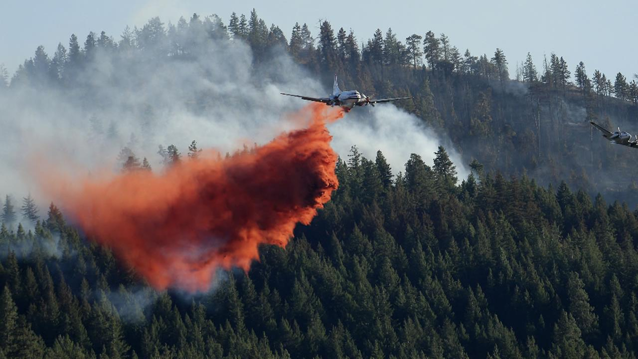 Guided by a spotter plane at right, an airplane drops fire retardant while fighting a wildfire near Twisp, Wash. Friday, Aug. 21, 2015.