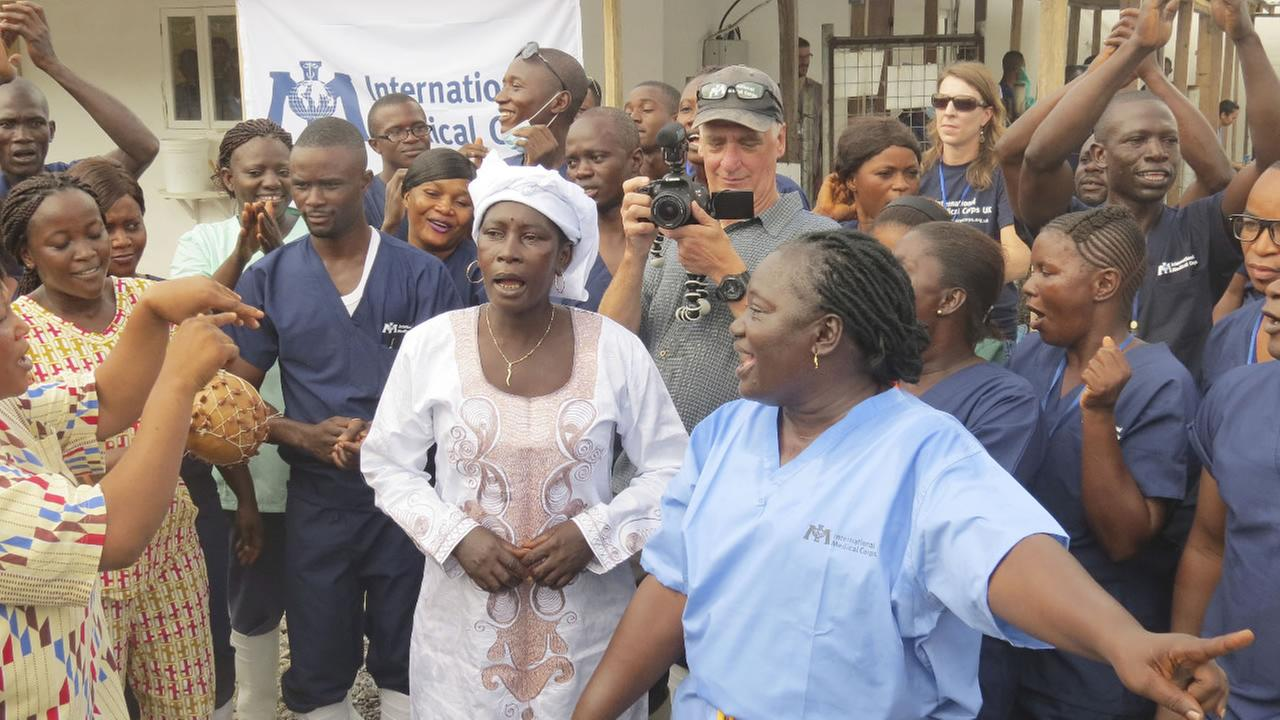 Adama Sankoh, 40, centre, who contracted Ebola  late last month stands with health officials the moment after she was discharged from a treatment center in Sierra Leone.