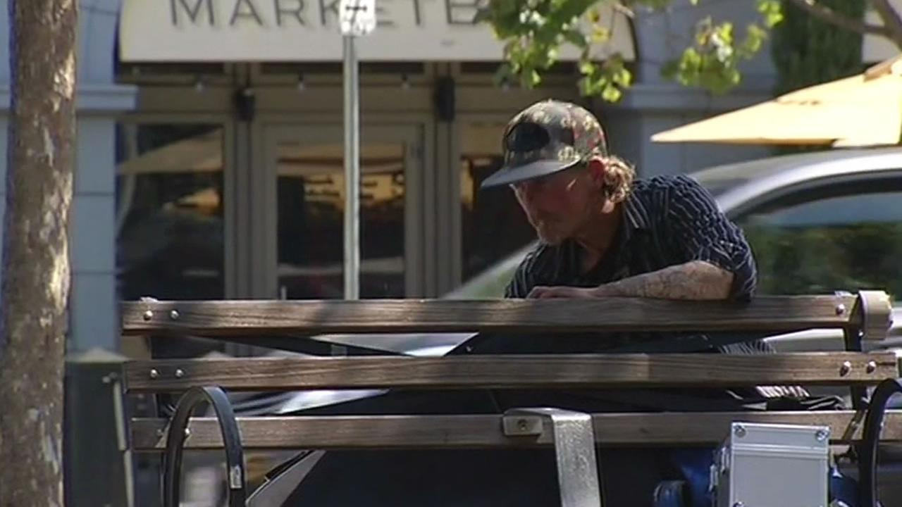 homeless man sits on a bench