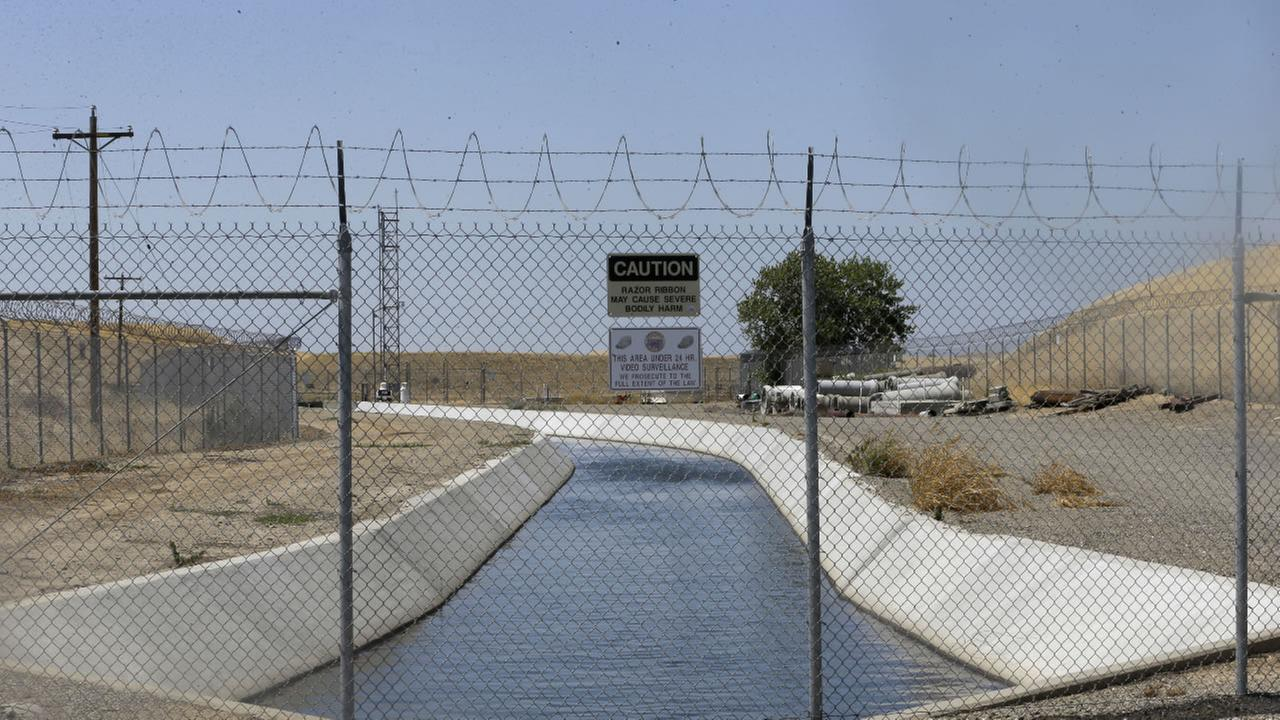 In this photo taken Tuesday, July 21, 2015, water flows down a diversion canal operated by the Byron-Bethany Irrigation District near Byron, Calif.