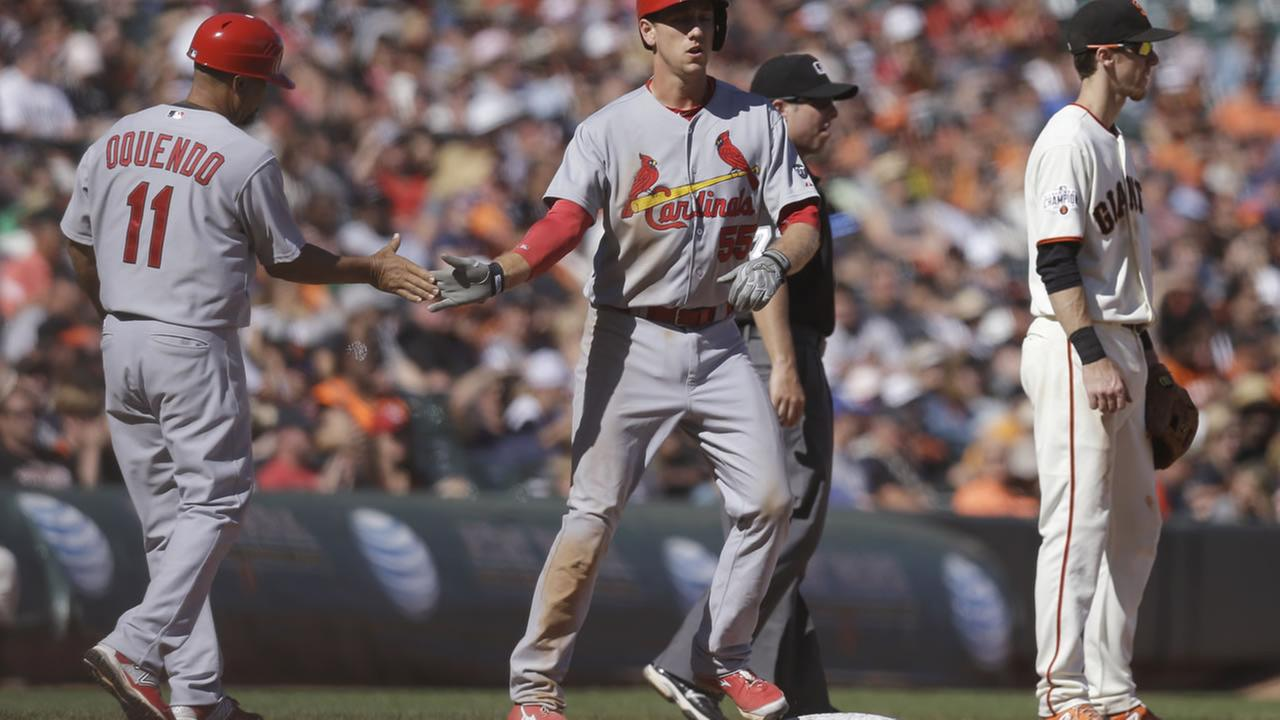 St. Louis Cardinals Stephen Piscotty, center, is congratulated after hitting an RBI triple against the Giants during a baseball game Saturday, Aug. 29, 2015, in San Francisco.
