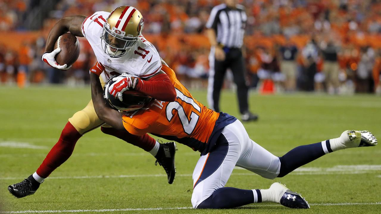 San Francisco 49ers wide receiver Quinton Patton (11) is hit by Denver Broncos cornerback Aqib Talib (21) during an NFL preseason football game, Saturday, Aug. 29, 2016, in Denver.