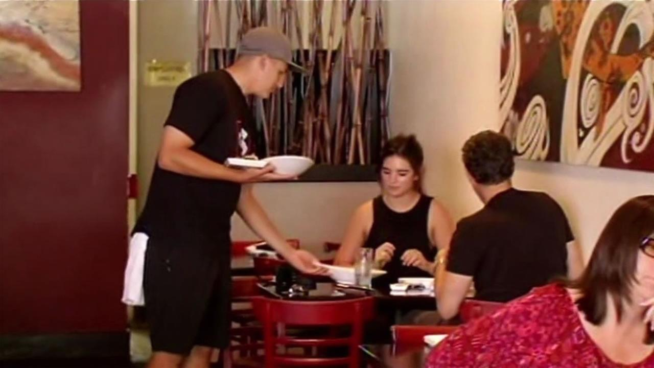 A server hands food to customers at Sushi Confidential in Campbell, Calif., Sept. 3, 2015.