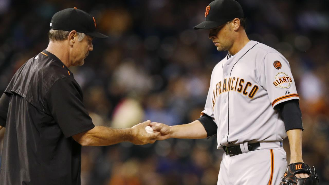 San Francisco Giants manager Bruce Bochy, takes ball from starting pitcher Ryan Vogelsong as he is removed from the game after giving up an RBI-single to Colorado Rockies.