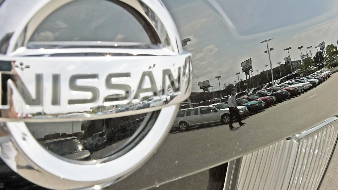 FILE - A Nissan dealership is reflected in the hood of a car in this July 25, 2005 file photo taken in West Allis, Wis.