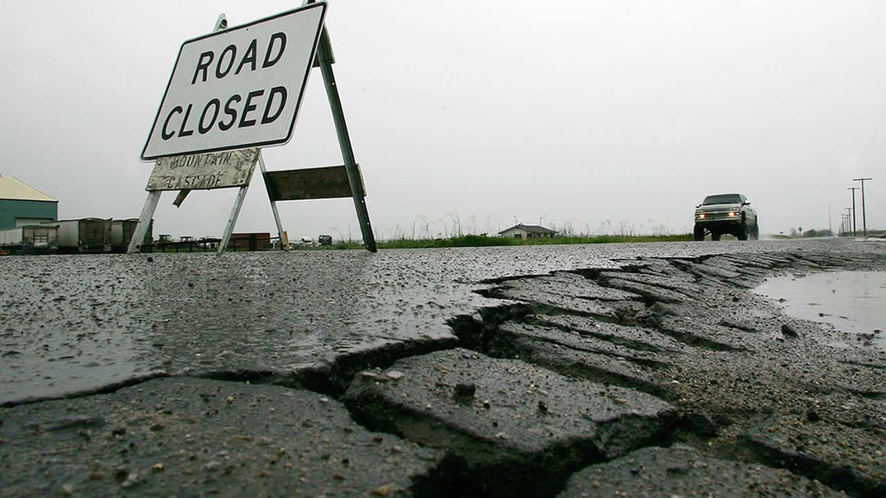 Potholes and road closure are visible at the corner of Enterprise and Paige Avenues, April 3, 2006 in Tulare, Calif. (AP Photo/Gary Kazanjian)
