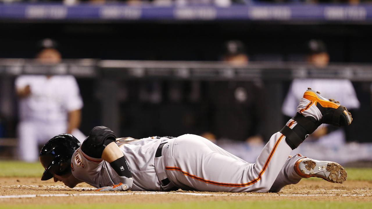 San Francisco Giants Buster Posey falls in the batters box after fouling a pitch of his foot during the fifth inning against the Colorado Rockies in a baseball game Sept. 4.