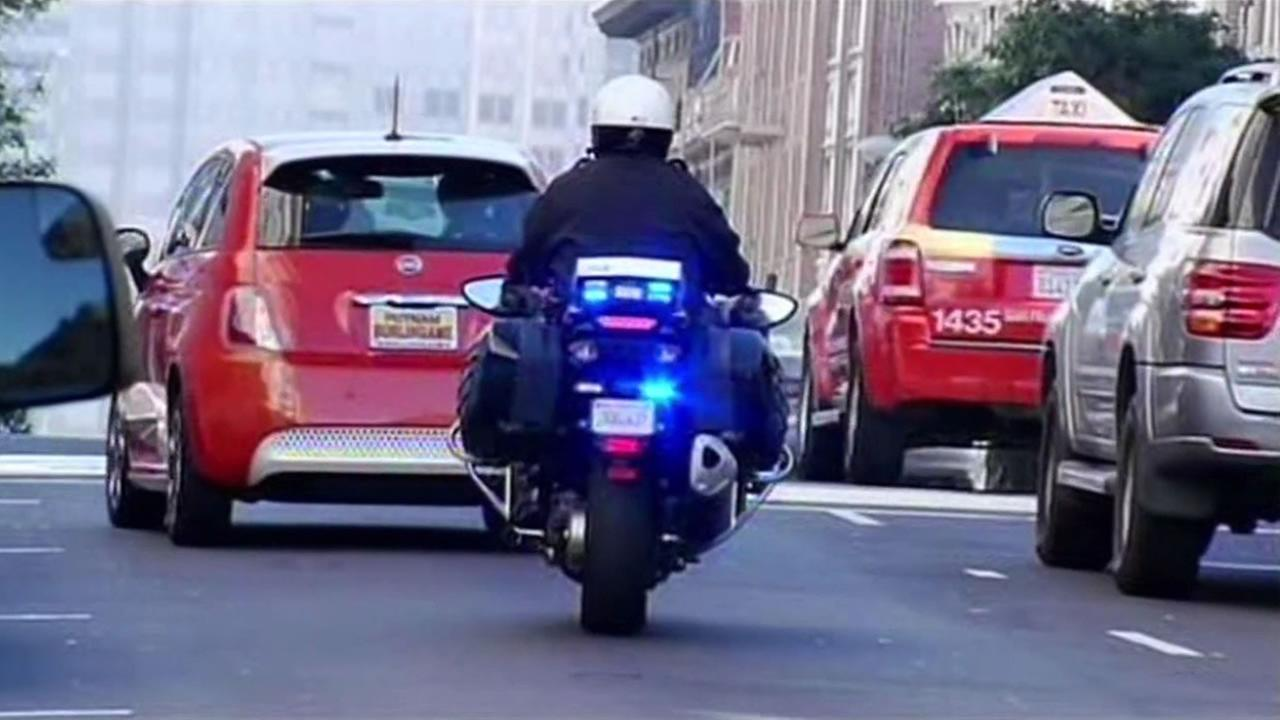 San Francisco police officer signals to a motorist to pull over.