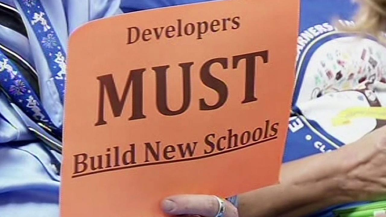 a sign that reads developers must build more schools