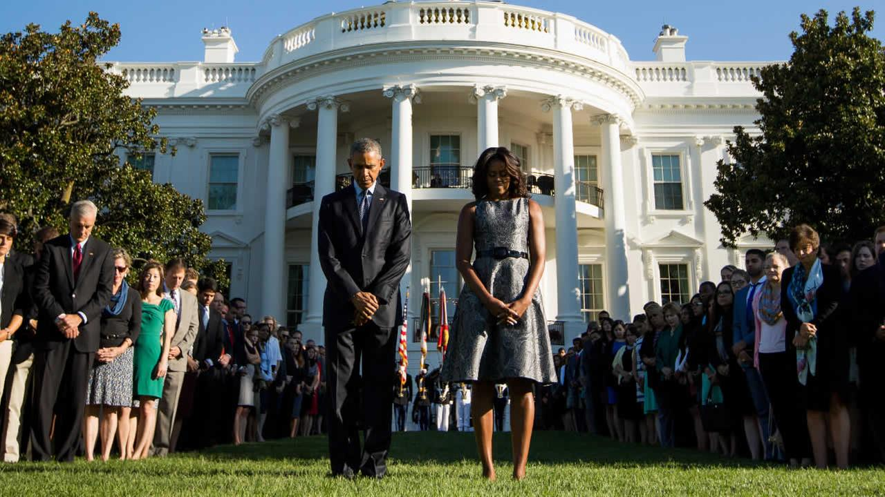 President Obama and first lady Michelle Obama observe a moment of silence to mark the 14th anniversary of the 9/11 attacks at the White House in Washington, Friday, Sept. 11, 2015.