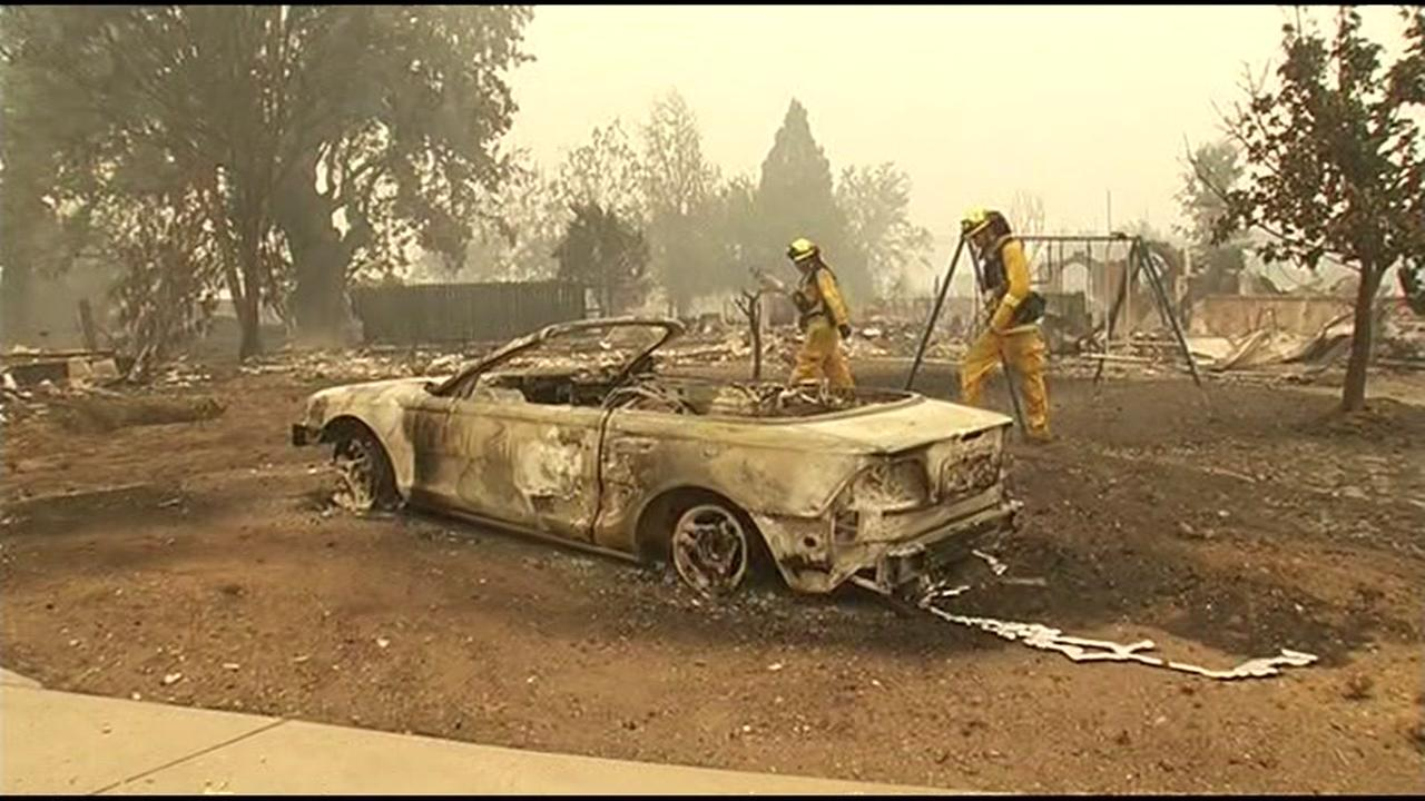 The Valley Fire in Lake County, Calif. burned thousands of acres on Sunday, September 13, 2015. Firefighters stand next to a burned car.KGO-TV