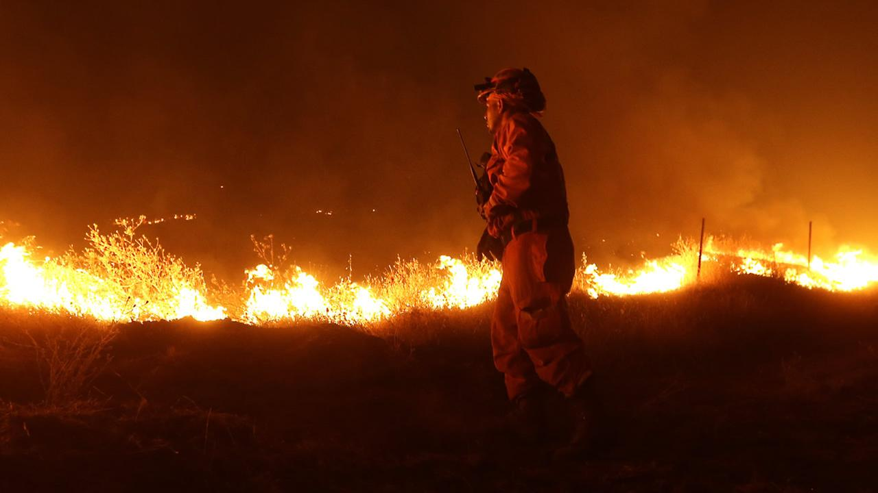 An inmate from the California Department of Corrections and Rehabilitation stands guard as flames from the Butte Fire approach a containment line on Sept. 12, 2015. (AP Photo)