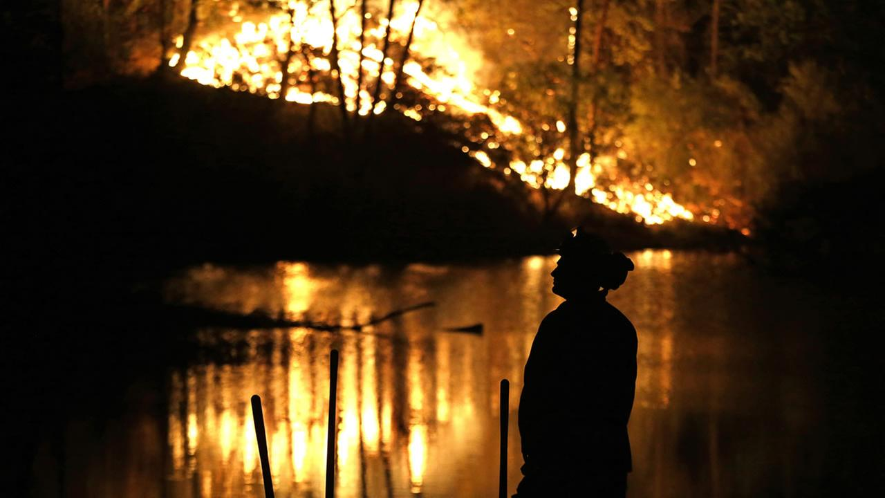 A firefighter stands near a wildfire in Middletown, Calif., on Sunday, Sept. 13, 2015. AP Photo/Elaine Thompson
