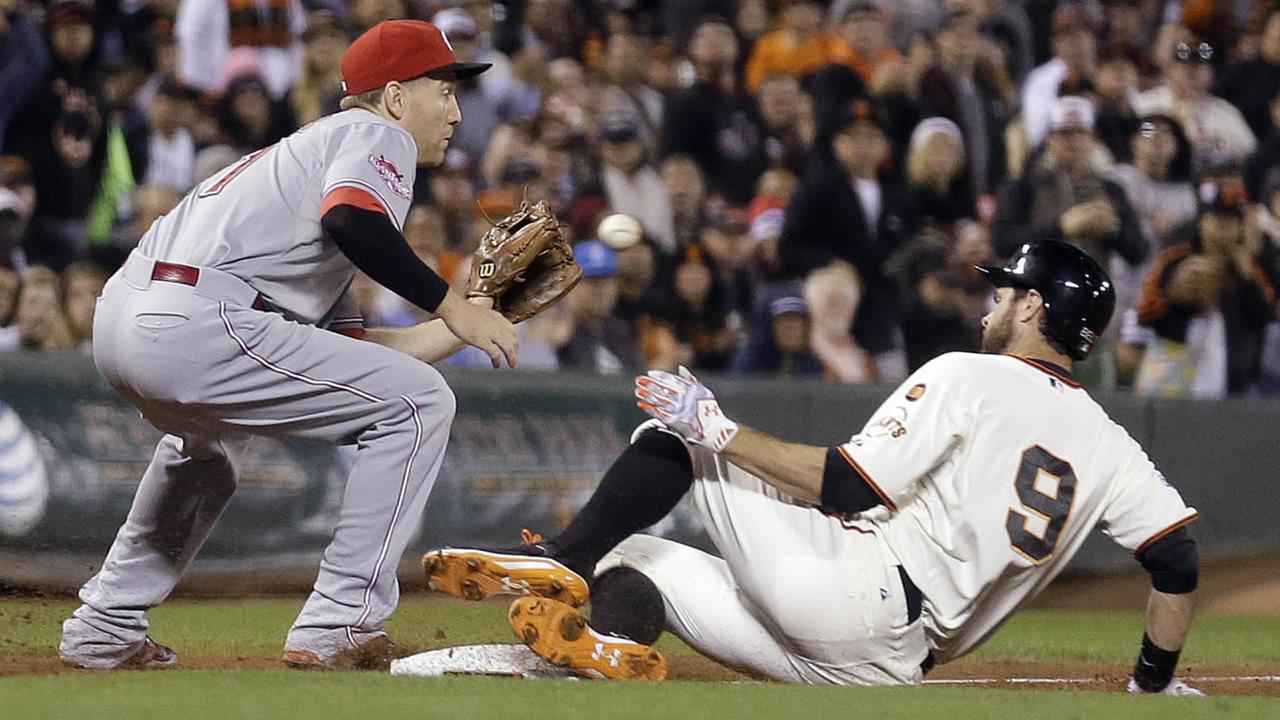 Giants Brandon Belt slides safe beneath the tag of Reds Todd Frazier with an RBI triple in the third inning of a baseball game Monday, Sept. 14, 2015. (AP Photo)
