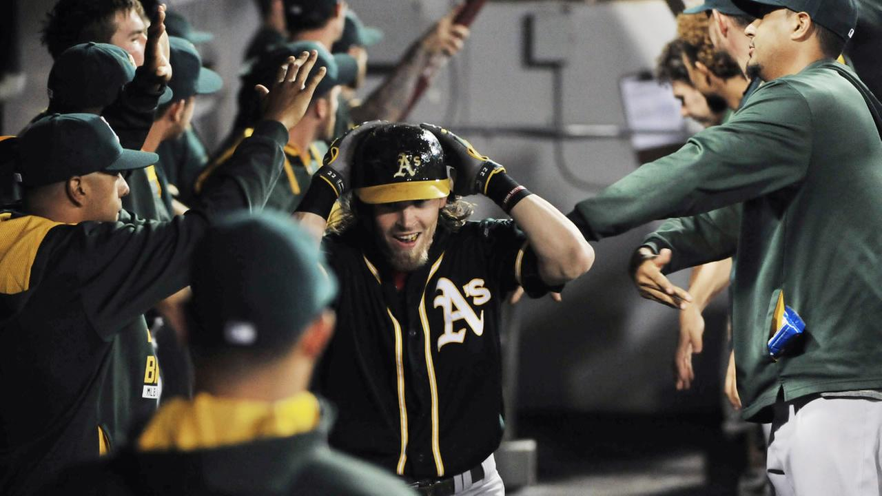 Oakland Athletics Josh Reddick, center, is greeted by teammates after hitting a two-run home run against the Chicago White Sox Tuesday, Sept. 15, 2015, in Chicago.